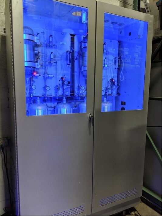 Large industrial cabinet with stainless steel tanks and pipes with ultraviolet lighting